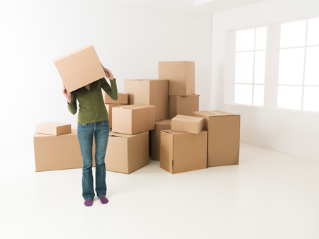 42861783 - woman moving in new house, having fun hiding her head in cardboard box