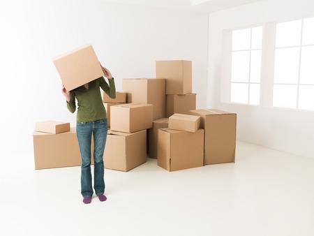 42861783 - woman moving in new house, having fun hiding her head in cardboard box